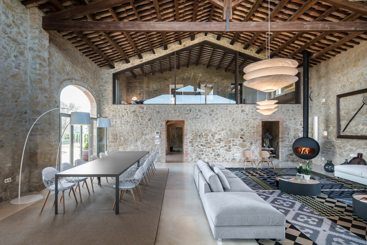 BUBBLE WOOD FIREPLACE BY ANTRAX WARMS THE LIVING AREA OF A STYLISH FARMHOUSE IN GIRONA, SPAIN